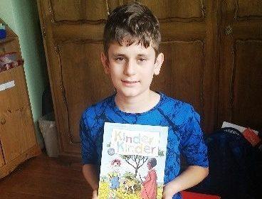 Ein Junge hält eine Kinderzeitschrift in den Händen