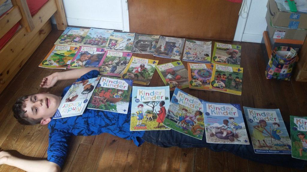 """Ein Junge liegt auf dem Boden und hat sich mit """"Kinder, Kinder""""-Heften zugedeckt (Quelle: privat)"""