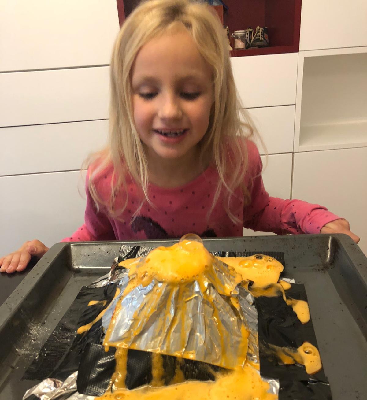 Ein Mädchen schaut auf seinen selbst gebastelten Vulkan aus Alufolie, aus dem gelber Schaum quillt (Quelle: Katharina Baumgartner)