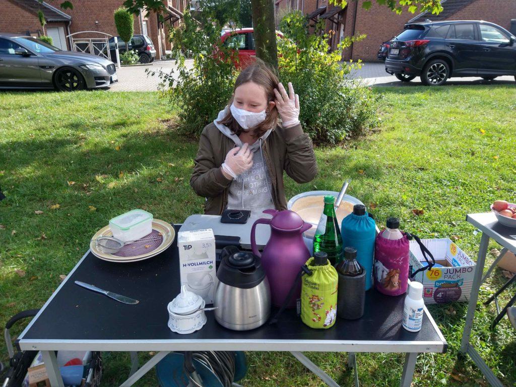 Ein Mädchen steht hinter einem Tisch mit Kaffeekannen und Waffelteig